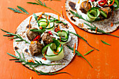 Wraps with spicy meatballs, cucumber and rocket