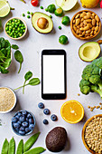 Vegetables, fruit, lentils and almonds arranged around a smartphone