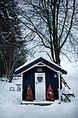 Weihnachtlich dekoriertes Gartenhäuschen im Schnee