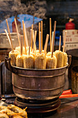 Pan of hot corn on sticks in a basket, Beijing, China