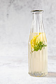 Cold peppermint tea with lemon in a glass bottle