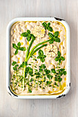 An unbaked focaccia with a flower picture made of herbs, spring onions and garlic