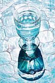 Wasserglas auf Fliesenboden