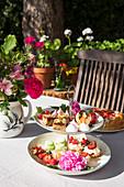 Küchlein, Obst und Blumen auf einer Etagere im sommerlichen Garten