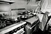 Koch beim dampfenden Herd in einer Restaurantküche