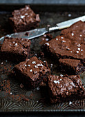 Chocolate brownies dusted with cocoa powder and sprinkled with sea salt