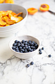 A bowl of blueberries with a bowl of apricots in the background