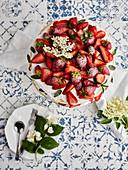 Pavlova cake with fresh strawberries garnished with fresh mint leaves and elderflower