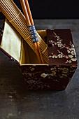 An oriental silk box with a bamboo mat and chopsticks