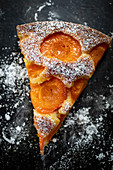 A slice of apricot cake dusted with icing sugar