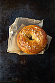A sesame seed bagel on a piece of paper