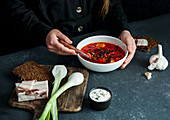 Borsch (Red beetroot soup) with girls hands, russian and ucranian food