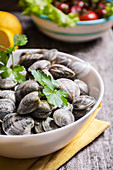 A dish of clams on the table ready to cook
