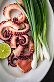 Grilled octopus with spring onions and limes