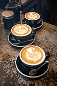Cappuccinos with milk foam patterns (latte art)