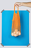 Hand carrying orange net sack with fresh eggs against blue rectangle during zero waste shopping