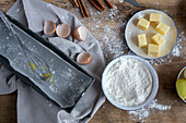 Ingredients for cake recipe including bowl with flour and egg placed on dusted wooden table