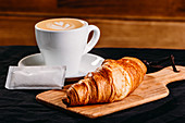 Golden crispy croissant served on wooden board with white cup of fresh coffee