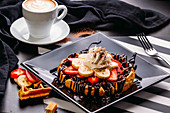 Cappuccino in white mug on table with plate of round waffle with banana and strawberry topped with chocolate sauce and whipped cream