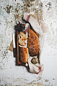 Rustic composition with aromatic bread loaves on board with linen towel and knife on shabby surface