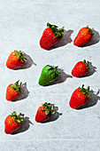 Fresh ripe red and green strawberries placed in gray table
