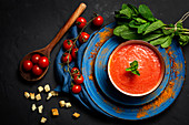 Healthy homemade tomato soup with bread, mint and olive oil on dark background