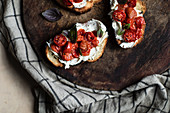 Grilled bread topped with cream cheese, cherry tomatoes and rhubarb
