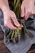 A man peeling green asparagus