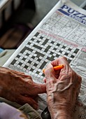 Care home resident doing a crossword puzzle