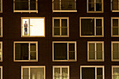 Solitary man in lit window