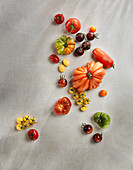 Various colourful tomatoes on a stone surface