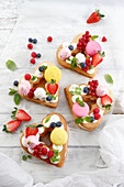Heart-shaped cakes with meringue, fruit and macaroons