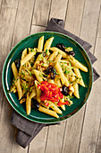 Penne pasta with peppers, tomatoes, courgettes and black olives