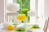 Easter table set in spring colours with paper flowers, feathers and narcissus