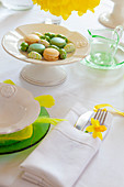 Macaroons on a spring-themed Easter table decorated with daffodils and feathers