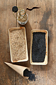 Black and white sesame seeds in rectangular bamboo containers