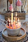 Viele brennende Kerzen in Napfkuchenform mit Sand