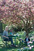 Sitzgruppe unter Zierapfelbaum 'Paul Hauber', Frau mit Kaffeetasse, Junge sitzt und liest, Hund Zula