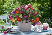 Bunter Strauß aus Tulpen und Purpur-Ginster im Korb als Tischdekoration