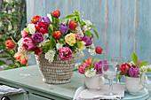 Bunter Strauß aus Tulpen und Traubenkirsche im Korb