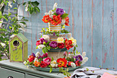 Selbstgebaute Etagere mit Tulpenblüten, Blüten der Traubenkirsche und Ranken der Klettergurke