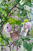Kleine Flaschen mit Ranunkelblüten und Wolfsmilch an Baum gehängt