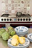 Quitten, Artischocken und Teller auf Edelstahltisch in der Küche