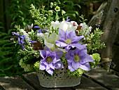 Frühlingsgesteck mit Clematis 'Cezanne', Tulpen, Schneeball, Traubenhyazinthen und Zweigen