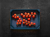 Cherry tomatoes on vines in a wooden crate