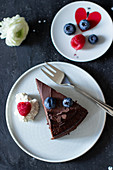 A slice of chocolate cake with ganache and fresh berries