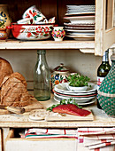 Salmon and bread amongst ethnic crockery on dresser
