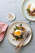 Poached egg on toast with asparagus, ham, parmesan cheese and thyme