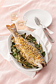 Stuffed trout with a crispy crust on a bed of bay leaves