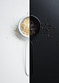 Weißer und schwarzer Reis im Sieb auf schwarz-weißem Untergrund